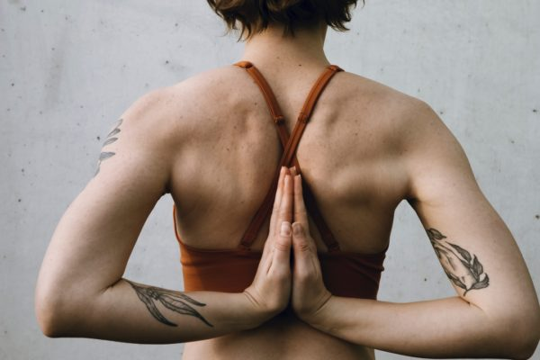 woman crossing arms behind back in yoga pose
