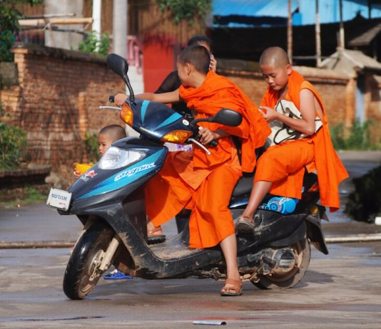 boys in orange buddhist robes riding scooter bike