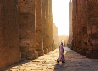 lone woman in sunny egyptian temple
