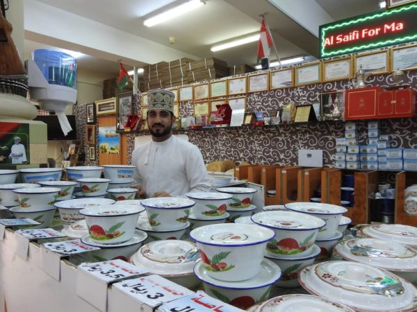 man hehind souk counter in oman