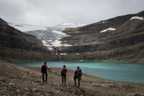 three hikers before a glacial lake