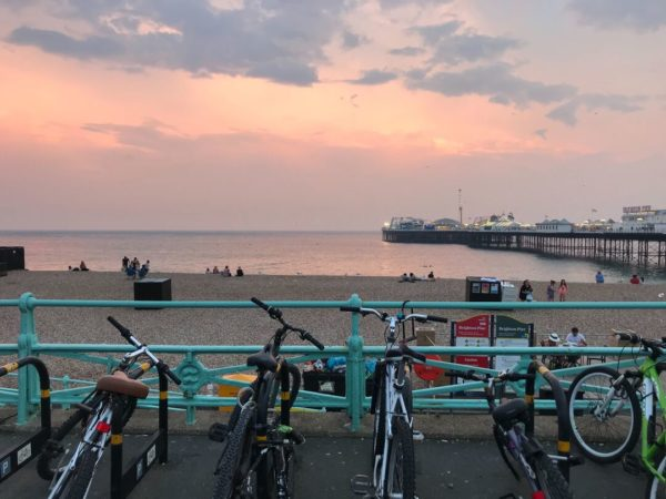 bikes parked along blue railing at seaside sunset
