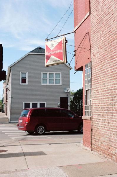 budweiser sign over street corner bar