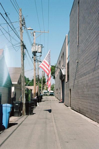 american flag hanging in alleyway