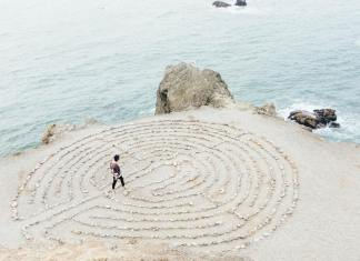 person walking in labyrinth by ocean