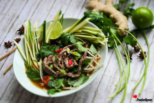 A bowl of zucchini noodles, topped with fresh herbs (like coriander, mint, basil) and sliced beef and covered with beef aromatic beef broth. Some juicy limes on a side.