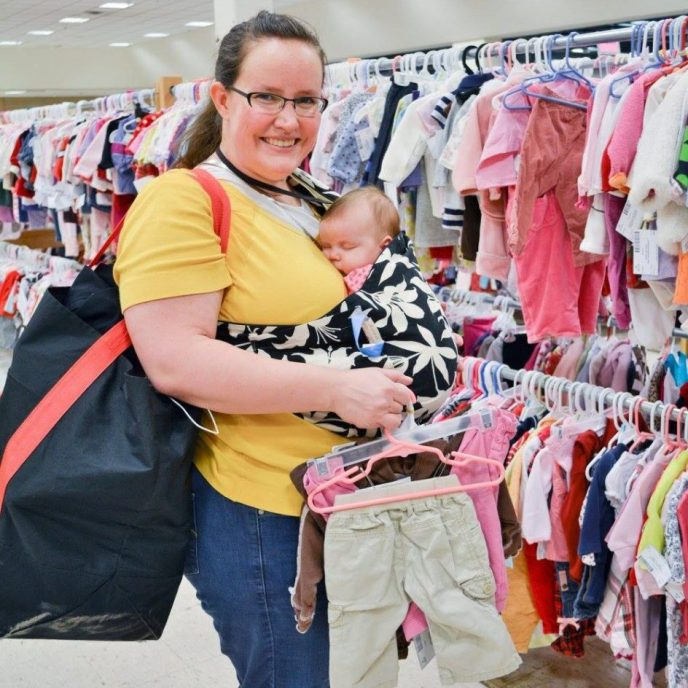 Happy shopper with bag full of stuff, mom carrying baby in sling
