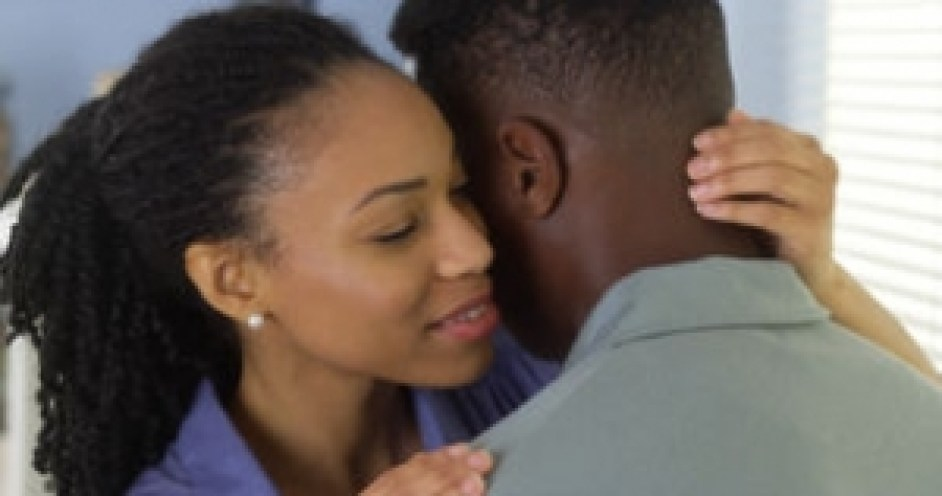 young-black-woman-holding-boyfriend-women-whispering-to-his-ear-46737566