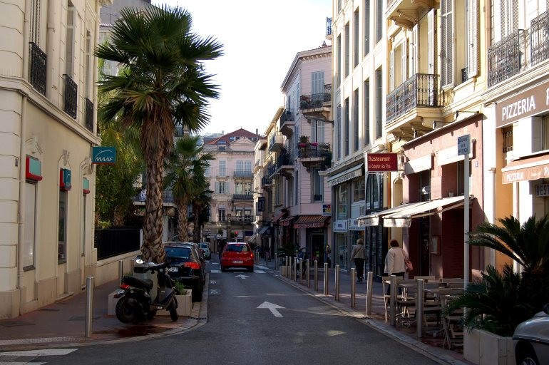 A lovely street in Cannes, France, lined with shops, balconies and palm trees
