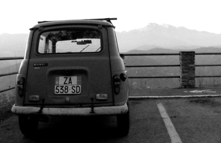 Vintage Renault parked overlooking a valley in Italy