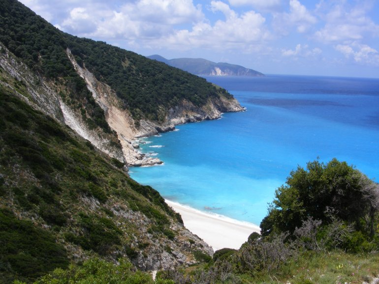 A beautiful view through a valley of Myrtos Beach, with white pebbles against a stunningly beautiful bright turquoise ocean in a bay surrounded by cliffs and green vegetation looking out to the coastline beyond
