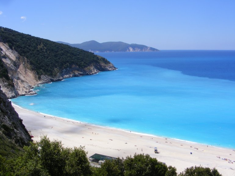 A view out to sea at Myrtos Beach, with stunning backdrop of the coastline in the distance and vivid turquoise sea and white pebbles in the foreground