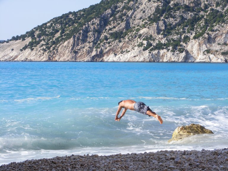 A man dives into turquoise waves on Myrtos Beach in Kefalonia, Greece
