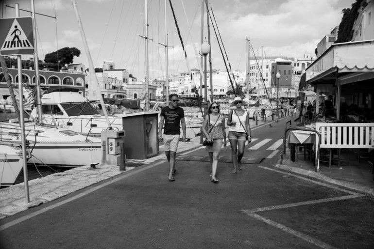 Tourists stroll along harbour in Ciutadella in Menorca