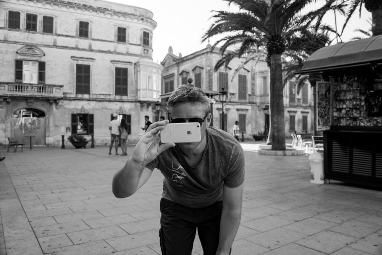 Man takes photo with Apple iPhone on rustic street in Old Town Ciutadella in Menorca