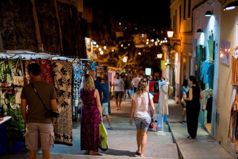 Women shop at night market stalls in Menorca's Ciutadella