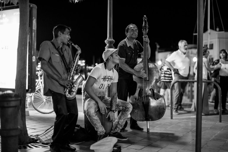 Band with saxophone and double bass play in street in Menorca's Ciutadella