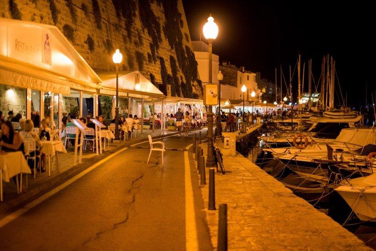 Busy restaurants line Menorca's Ciutadella harbour at night