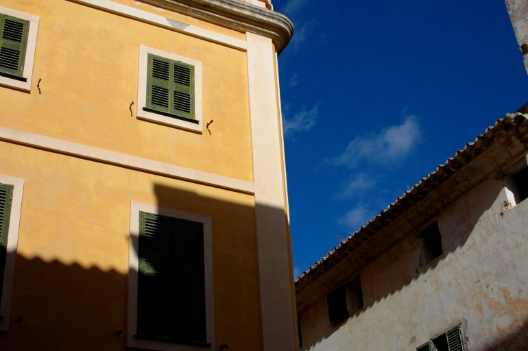 Yellow building with green shutters against blue sky