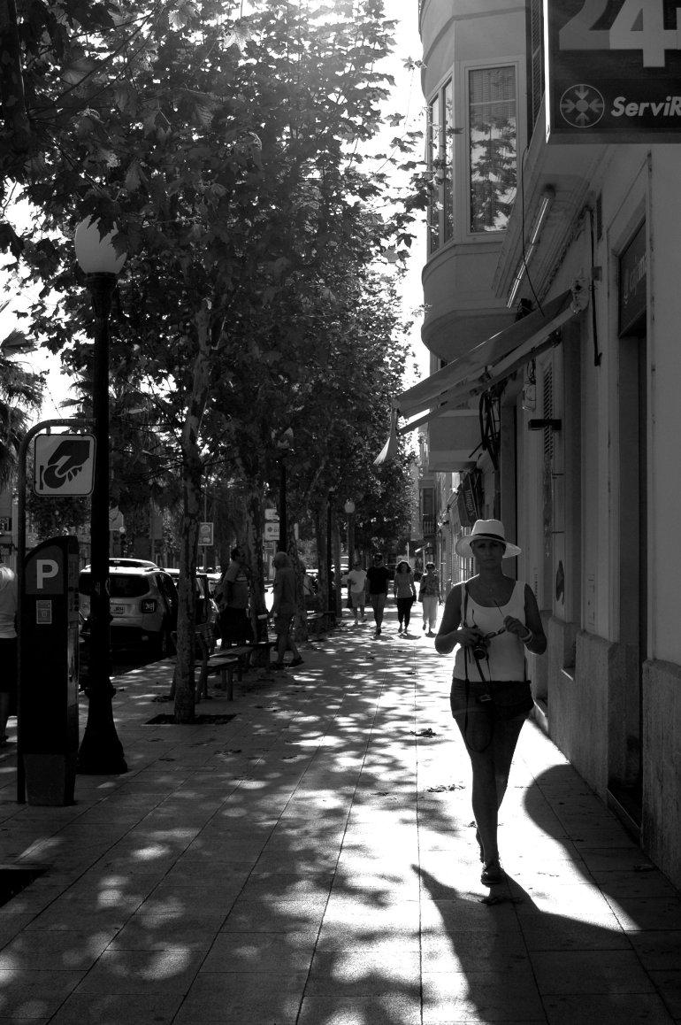 Girl wearing white hat walks down street in Menorca, Spain