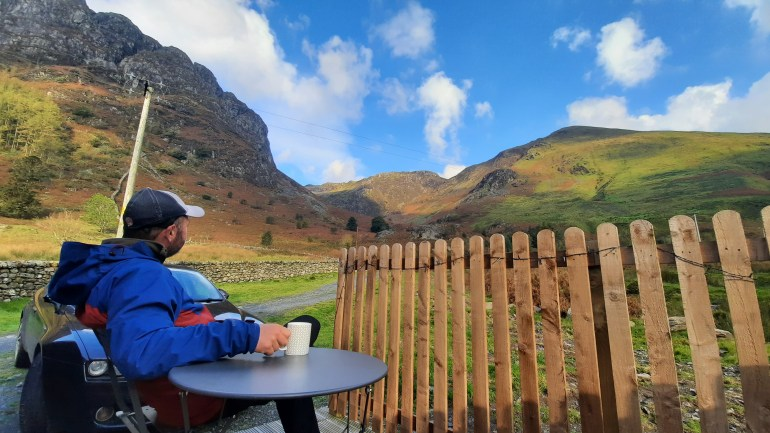 A man sits on the deck of a log cabin with a coffee gazing out at the mountainous scenery around him