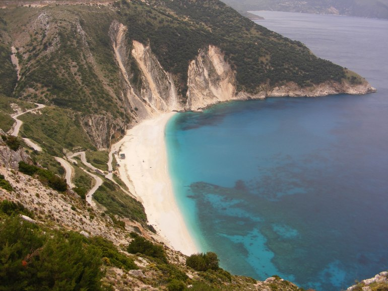 Looking over Myrtos Beach in Kefalonia, from above with white pebbles against a deep blue calm sea, surrounded by green cliffs