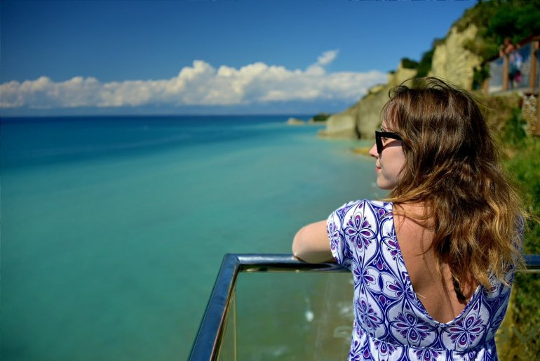 Girl on glass balcony looks out over turquoise sea and cliffs at Logas Beach in Corfu