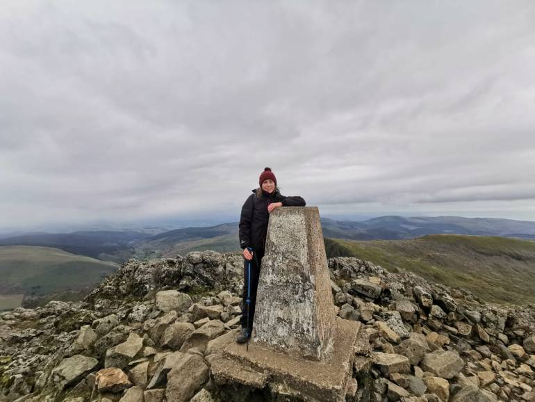 Girl stands at the summit of Cadair Idris in Snowdonia, Wales