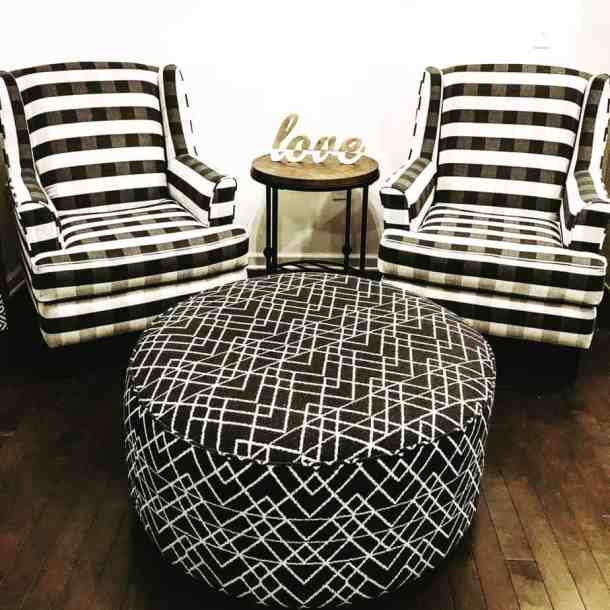 Black and white chairs and an ottoman in an organized living room