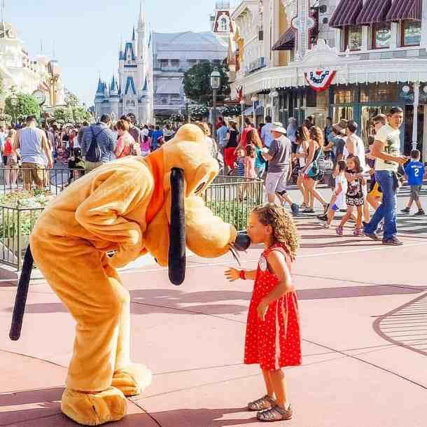 Disney Park crowd and Pluto at Magic Kingdom