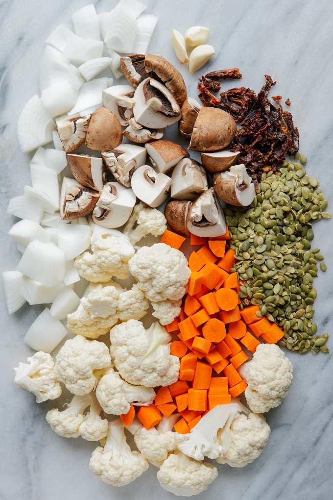 raw ingredients for vegan sausage crumbles - onion, mushrooms, sun-dried tomatoes, garlic cloves, pumpkin seeds (pepitas), chopped carrots, and cauliflower florets