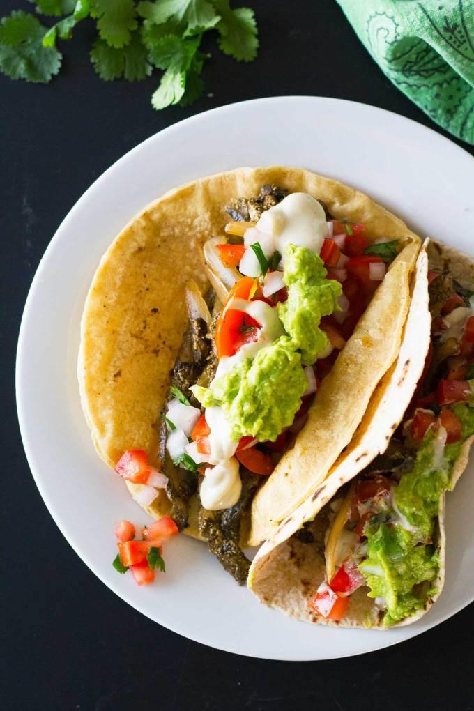 Ultimate Vegan Fajitas | Assembled fajitas on a plate topped with guacamole, pico de gallo, savory cashew cream | https://passtheplants.com/
