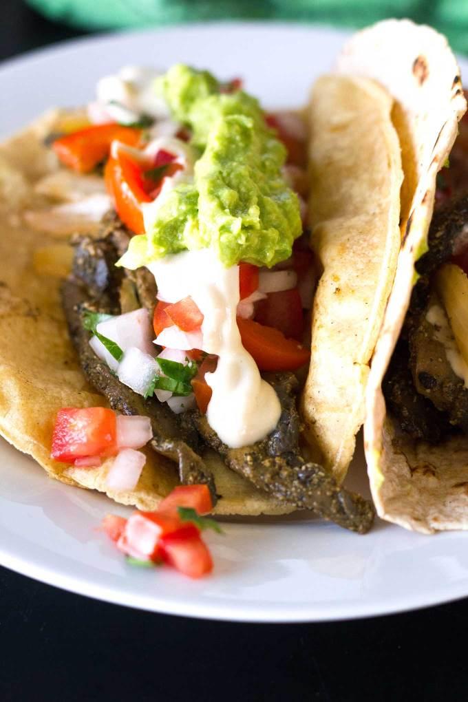 Ultimate Vegan Fajitas | Close-up of assembled fajitas on a plate topped with guacamole, pico de gallo, savory cashew cream | https://passtheplants.com/