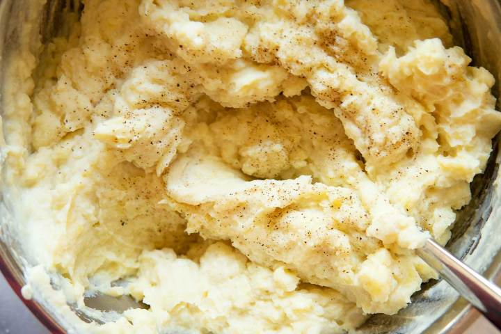 vegan mashed potatoes in a pan with cracked black pepper on top