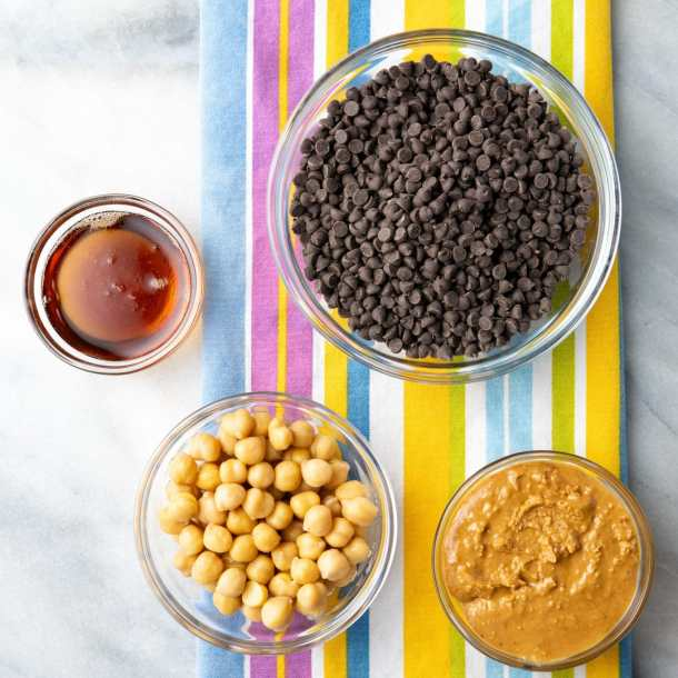 overhead shot of ingredients for vegan peanut butter cups - chocolate chips, maple syrup, chickpeas, peanut butter
