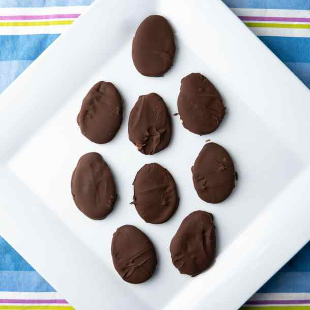vegan peanut butter eggs arranged in an egg-shaped pattern on a white plate