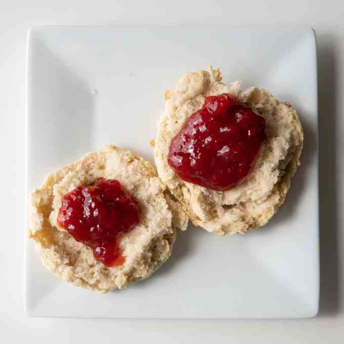 strawberry jam on biscuit halves on a white square plate