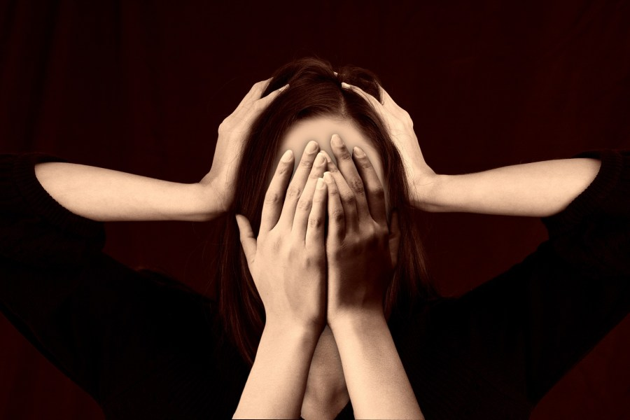 Woman crying into hands wuth hands around head #migraine