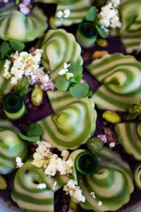 close up of spinach spiralled cappellacci filled with asparagus and mascarpone in a red cabbage broth with feta zucchini shiso pistachios