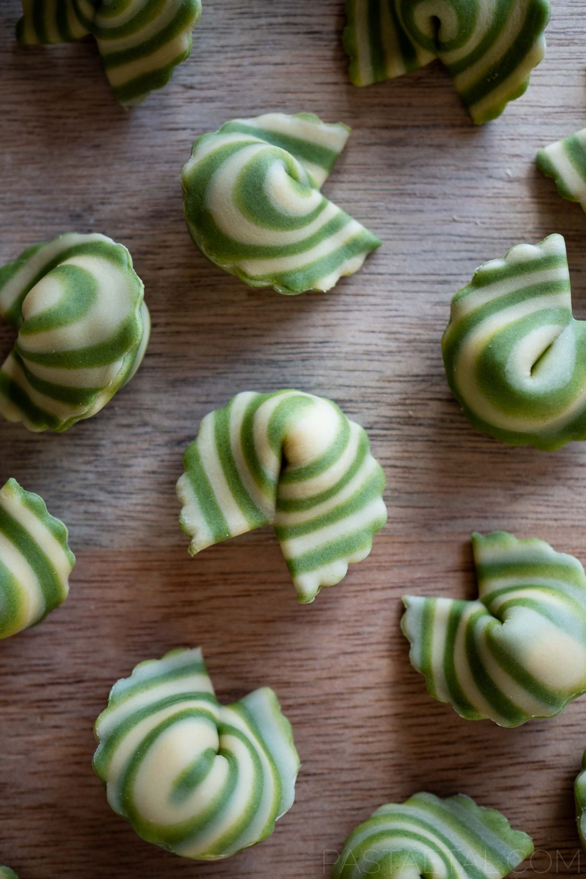 close up of spinach spiralled cappellacci filled with asparagus and mascarpone on a chopping board