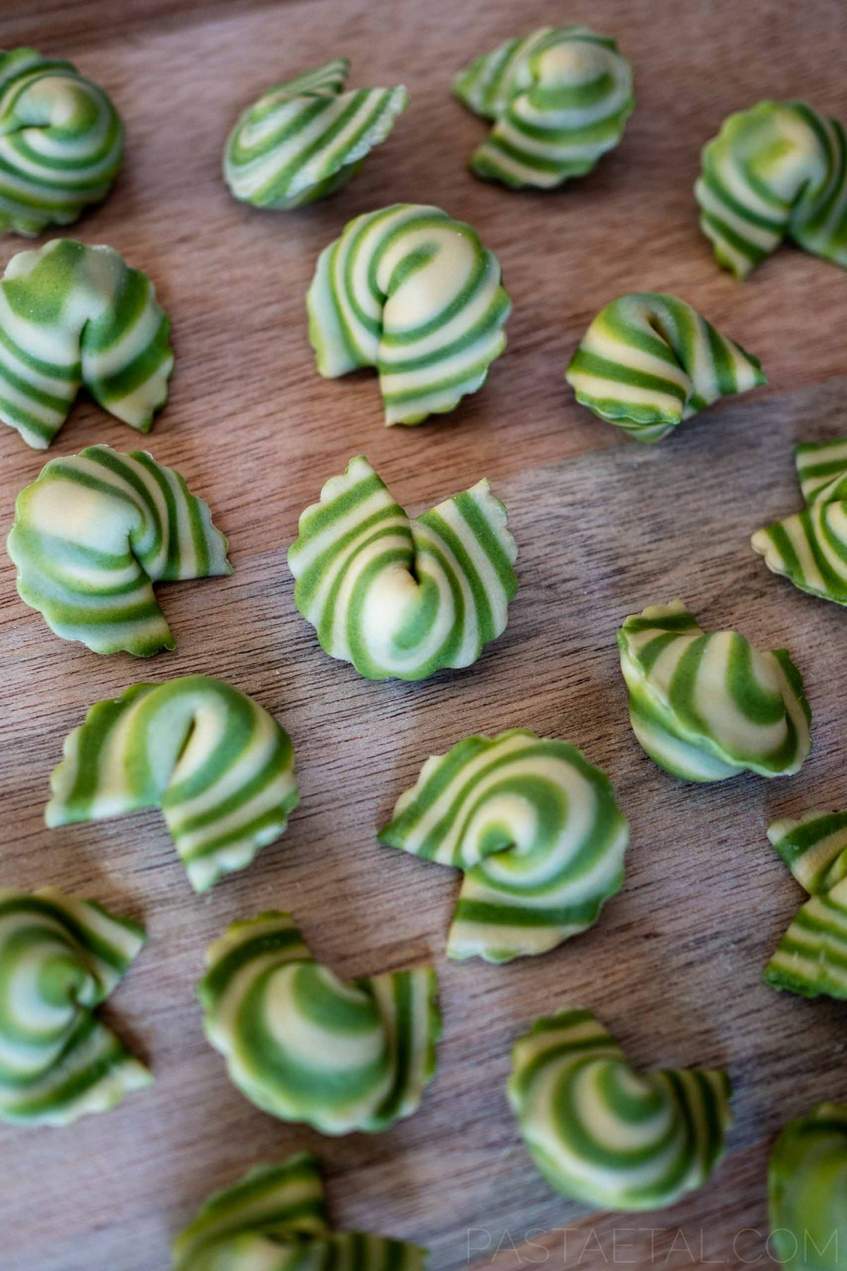 spinach spiralled cappellacci filled with asparagus and mascarpone on a chopping board