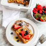 Easy Brioche French Toast on plate with bowl of berries