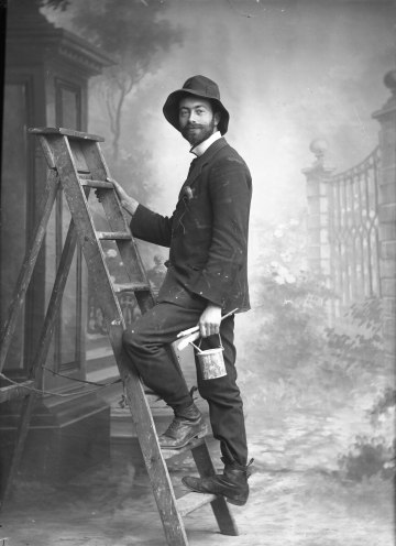 Knights-Whittome, posed in the studio 'painting' his backdrops.