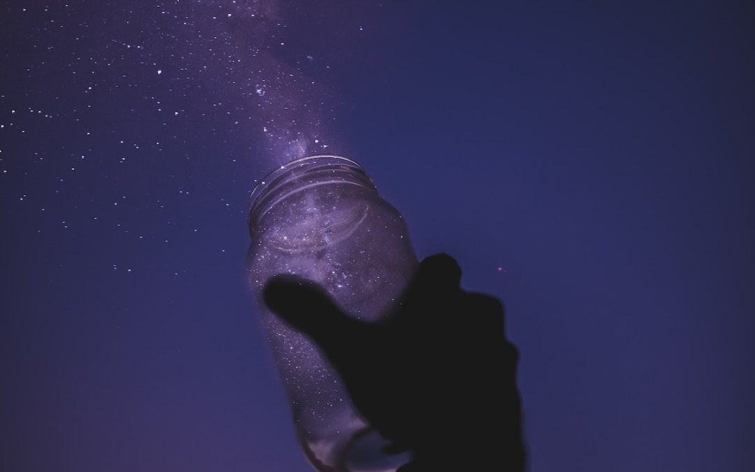 settling person holding jar of stars