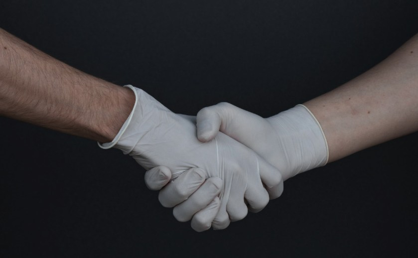 Shaking hands in latex gloves.