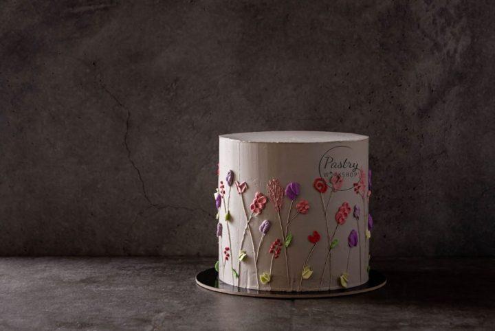Tort de eveniment imbracat in crema de unt, decorat cu flori din crema de unt