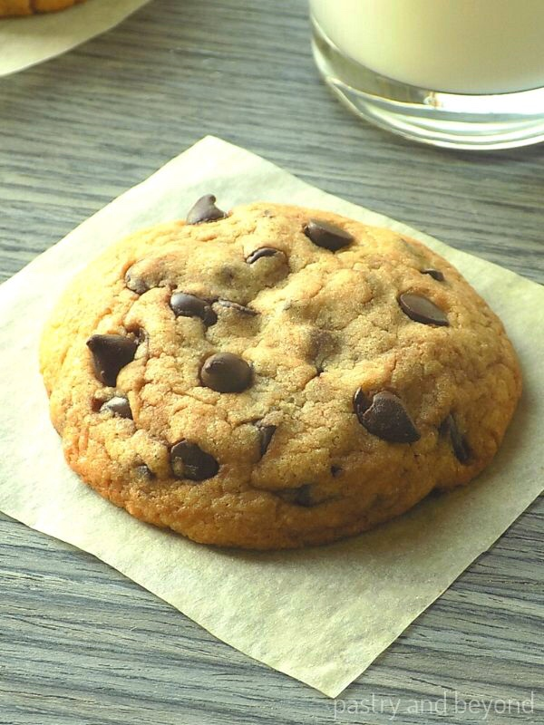 Chocolate chip cookie on a parchment paper with a glass of milk in the background.