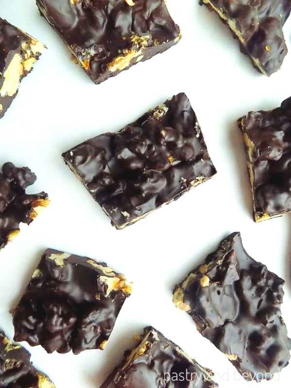 Chocolate Candy Bark cut into pieces on a white surface.