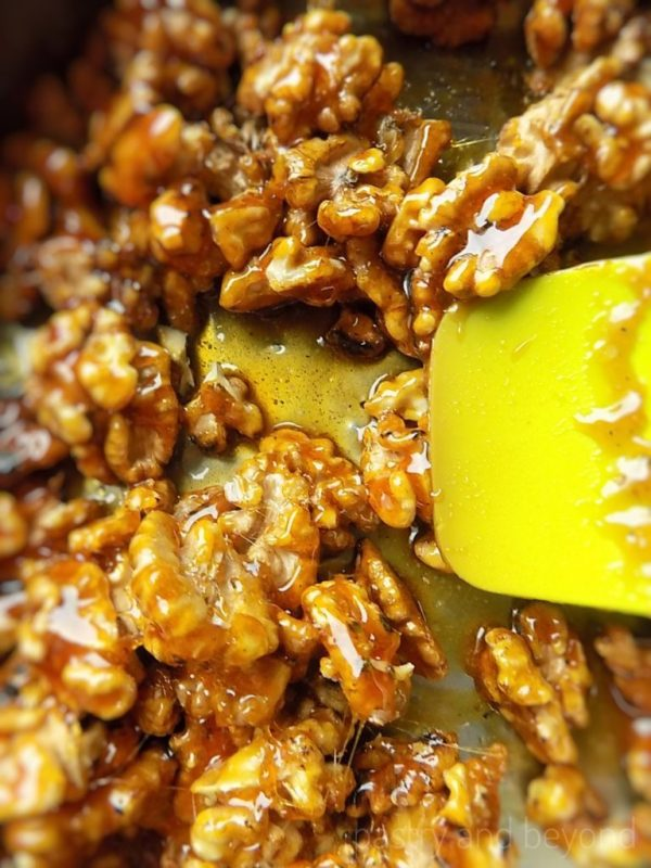 Mixing caramelized sugar with walnuts in a pan with a green spatula.