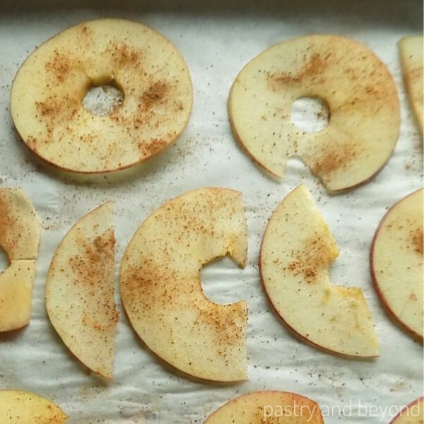 Thinly sliced apples with cinnamon on top on a baking sheet.